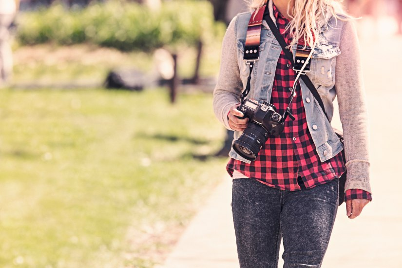 Woman in a plaid shirt and denim jacket holding a professional camera